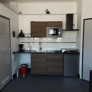 Keuken met keramische kookplaat, ijskast, magnetron, koffiezetapparaat, waterkoker enz